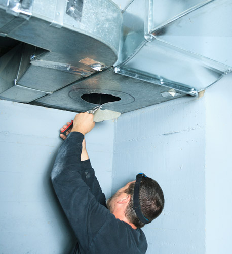 Serviceman Making an Opening in Ventilation System